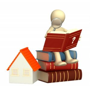 Puppet sitting on a stack of books that sits next to a small model white house with an orange roof, studying a book about mortgages