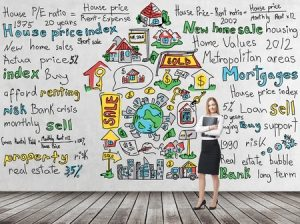 Full length beautiful woman in formal clothes holds a black folder. Colourful 'home sales' icons are drawn on the concrete wall. Risk analysis of the mortgage loan. Wooden floor.