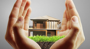 two hands cupping a two storeyed house sitting on green grass